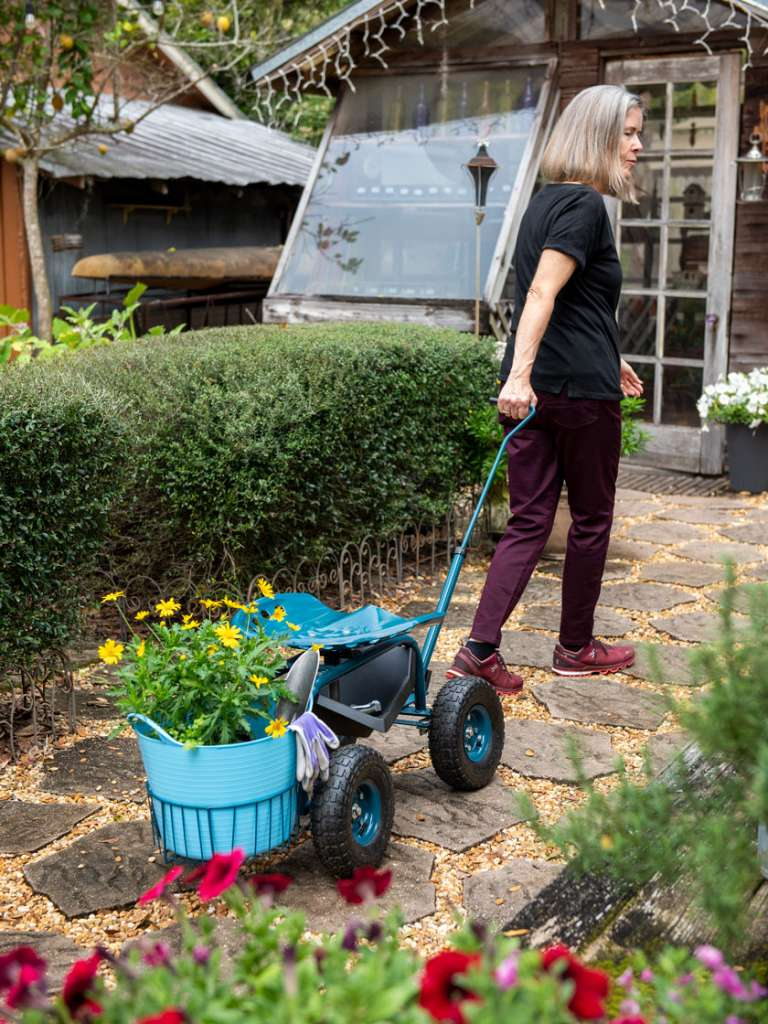 Женщина катит за собой тележку на участке - упражнения на даче для здоровья.