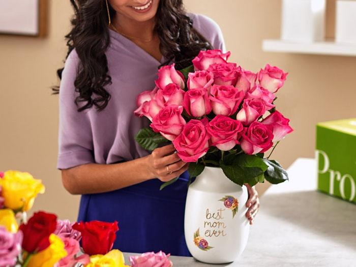 Девушка с букетом цветов в вазе. Как часто менять воду цветам.